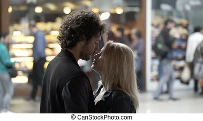 Young loving couple in kissing and talking in public on a street with people in background