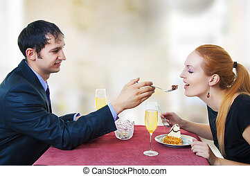 Young loving couple in restaurant.