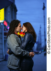 Young loving couple kissing in a city.