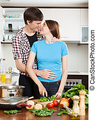 Young loving couple kissing in  kitchen