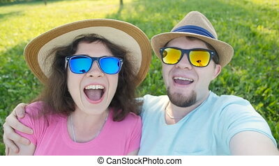 Young loving couple making selfie while lying on the grass -...