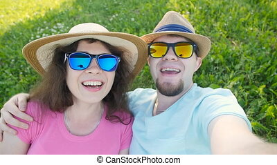 Young loving couple making selfie while lying on the grass
