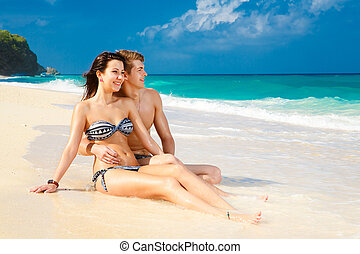 young loving couple on tropical beach - young loving happy...