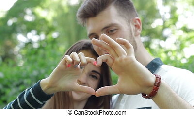 young loving couple shows hands symbol of the heart