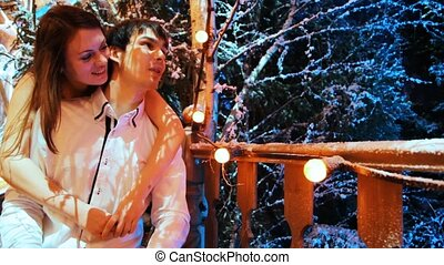 couple sits hugging on front porch decorated with lighted...