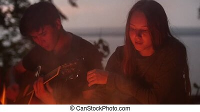 Young loving couple sitting by the bonfire and playing guitar in forest