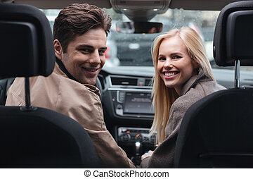 Young loving couple sitting in car looking camera.