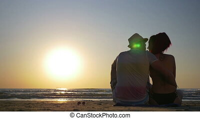 Young loving couple sitting on a beach and kissing