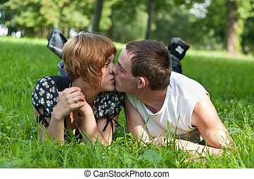 Young loving couple teenagers lying on green grass and kissing
