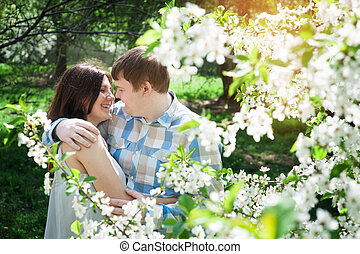 young loving couple walking in a spring garden