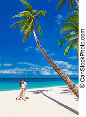 young loving happy couple  kissing at tropical beach with palm trees, wedding on beach