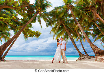 young loving happy couple on tropical beach with palm trees, wedding on beach