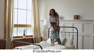 Young loving mother jumping on bed with happy child daughter.