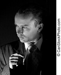 Young mafia member - Young man in suit smoking cigarette...