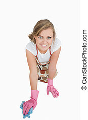 Young maid cleaning floor over white background