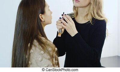 Young makeup artist apply makeup girl