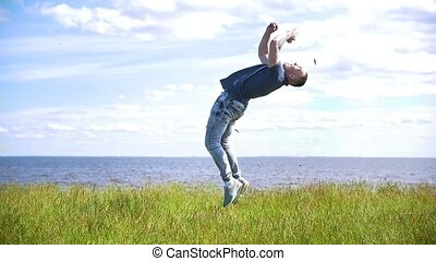 Young male acrobat performs flip on the hill over the river...
