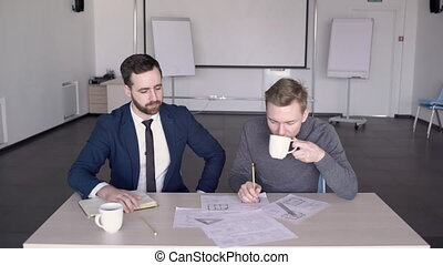 Young male architect is showing the project to his boss in modern conference room.