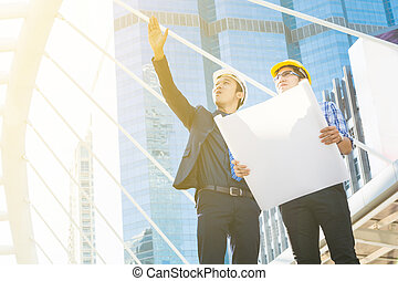 Young Male Architects Discussing with Businessman at Construction Site