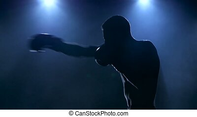 Young male athlete boxing in the studio visible in silhouette