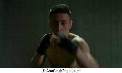 Young male athlete exercising kickboxing preparing to win...