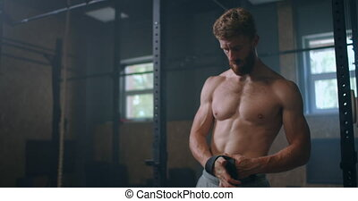 Young male athlete preparing himself for heavy lifting. Deadlift Weightlifting Wrist Straps Support For Bodybuilding And Powerlifting. the athlete trains in the gym, raises the bar. High quality 4k footage