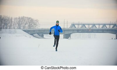 Young male athlete running fast in winter through the snowy ice field