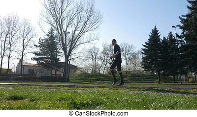 Young male athlete working legs before jog training