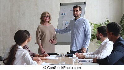 Young male bearded manager introducing pleasant middle aged skilled female supervisor trainer mentor to motivated young mixed race colleagues at business meeting workshop in modern workplace.