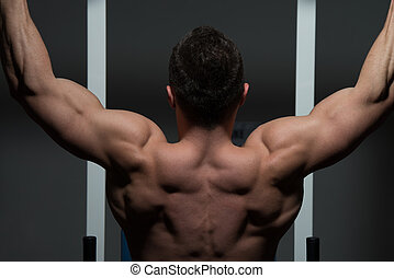 young male bodybuilder doing heavy weight exercise