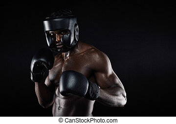 Portrait of a young male boxer in a fighting stance against black background. African young man in boxing gear ready to fight.