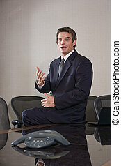 Young male business executive sitting in boardroom