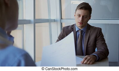 Young male businessman wrinkling the report of his female subordinate.