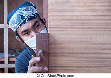 Young male carpenter take a planer with wood in workshop