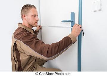 Carpenter Taking Measurement Of Door