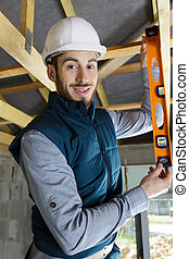 young male carpenter using spirit level on wooden beam
