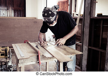 Young male carpenter working with wood in workshop