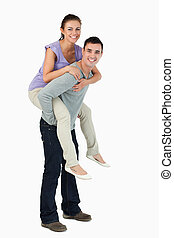 Young male carrying his girlfriend piggyback against a white...