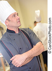 young male chef standing in restaurants kitchen arms crossed