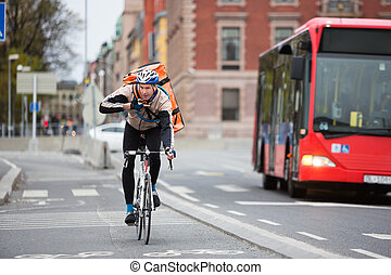 Young male cyclist with courier delivery bag using walkie-talkie while riding bicycle on street