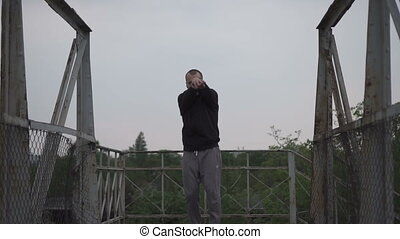 Young male dancing on the bridge