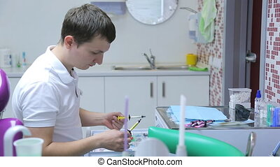 Young male dentist prepared to work at your workplace, choosing right tools.