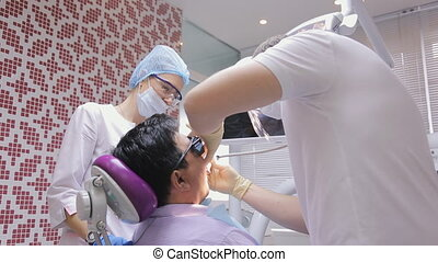Young male dentist treats patient's teeth using dental unit under supervision of a nurse.