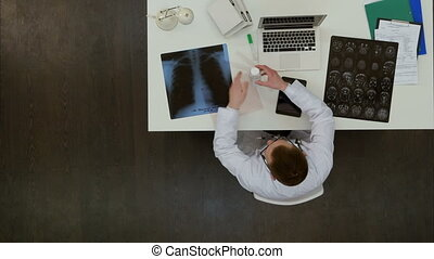 Young male doctor examining x-ray images at his desk