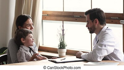 Side view friendly young male doctor giving high five to small kid patient, visiting clinic with mommy. Smiling woman mother holding on lap little son, chatting with pediatrician at hospital meeting.