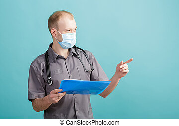 young male doctor holding a folder with papers on blue background