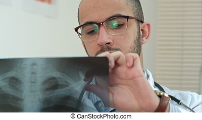 Young male doctor in glasses carefully analyzing xray image