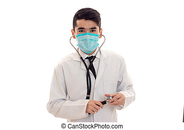 young male doctor in uniform and mask with stethoscope looking at the camera isolated on white background