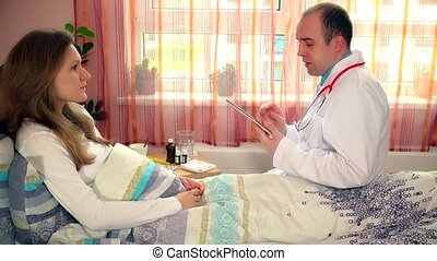 young male doctor using tablet computer to make records about female patient