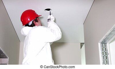 Young male electrician cutting holes in ceiling with...